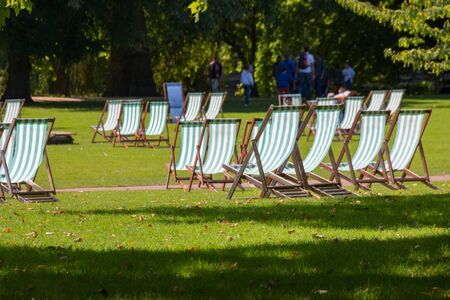 Comfortable deck chair inviting people to relax on summer day in beautiful St. James park, London, UK Imagens - 131942044