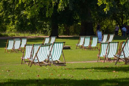 Comfortable deck chair inviting people to relax on summer day in beautiful St. James park, London, UK Imagens