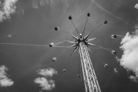 Black and white picture of amusement ride at chairoplane with flying people in front of a partly cloudy sky