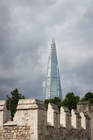London, United Kingdom – August 12, 2017: Top of the Shard skyscraper in London, UK during summer with parts of Tower of London in the foreground