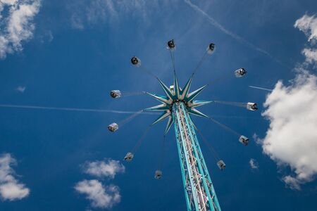Amusement ride at chairoplane with flying people in front of a blue and cloudy sky Imagens - 131941947