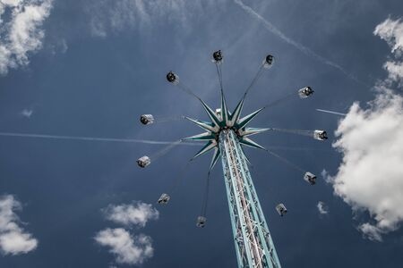 Amusement ride at chairoplane with flying people in front of a blue and cloudy sky Imagens - 131942307