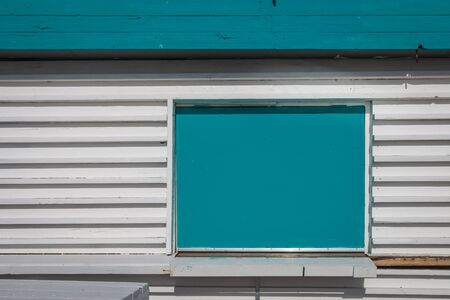 Wooden white sales booth with a closes turquoise window