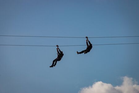 Two people having fun using a zip line at Scheveningen beach, the Netherlands in front of a blue sky
