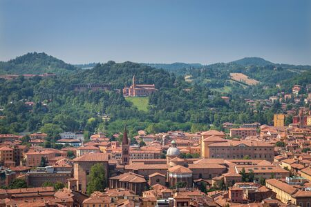 Aerial cityscape of Bologna, Italy with a view from the top of Asinelli tower to Basilica di San Petronio and Santa Maria della Vita church and green hills in the south of the city Standard-Bild