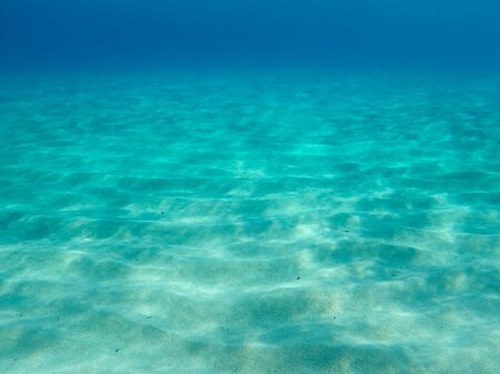 Sandy underwater sand on a shallow seabed in the Mediterranean sea with reflections of sunlight, natural scene, Sardinia, Italy Zdjęcie Seryjne - 143121669
