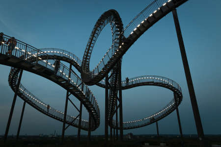 Duisburg, Germany – August 28, 2018: Fragment of walkable Tiger & Turtle roller coaster sculpture on Magic Mountain. The construction is an illuminated gangway with steps and part of industry culture