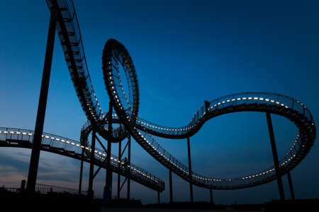 Duisburg, Germany – August 28, 2018: Fragment of walkable Tiger & Turtle roller coaster sculpture on Magic Mountain at night. The construction is an illuminated gangway with steps and part of industry culture