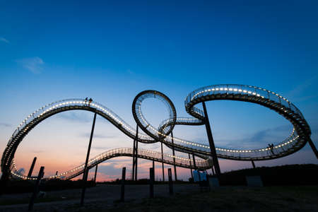 Duisburg, Germany – August 28, 2018: Walkable Tiger & Turtle roller coaster sculpture on Magic Mountain. The construction is an illuminated gangway with steps and part of industry culture