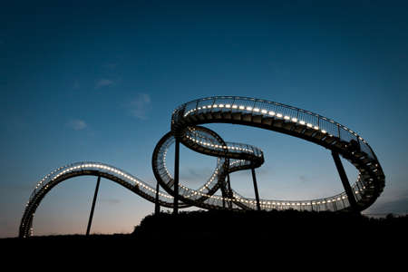 Duisburg, Germany – August 28, 2018: Walkable Tiger & Turtle roller coaster sculpture on Magic Mountain at night. The construction is an illuminated gangway with steps and part of industry culture