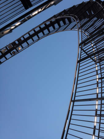 Duisburg, Germany – August 28, 2018: Fragment of walkable Tiger & Turtle roller coaster sculpture on Magic Mountain against sky. The construction is an illuminated gangway with steps and part of industry culture Publikacyjne