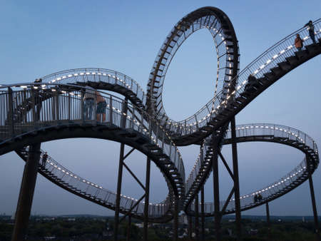 Duisburg, Germany – August 28, 2018: Walkable Tiger & Turtle roller coaster sculpture on Magic Mountain against sky. The construction is an illuminated gangway with steps and part of industry culture