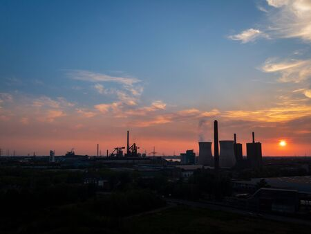 Scenic view of industrial landscape with power station and cooling tower at sunset against colorful sky Zdjęcie Seryjne