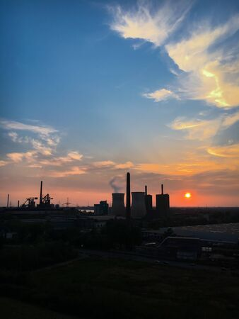 Scenic view of power station and cooling tower at sunset against colorful sky