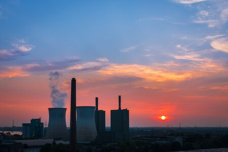 Scenic view of power station and cooling tower at sunset against colorful burning sky Zdjęcie Seryjne