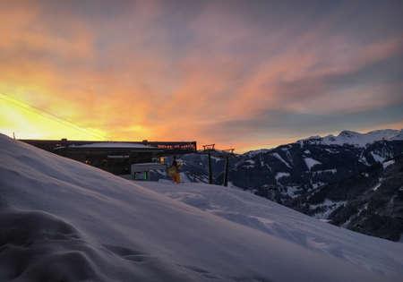 Vorderglemm, Austria – January 30, 2019: Arrival of Schönleiten cable car ski lift in the region of Saalbach-Hinterglemm against burning sky at sunset