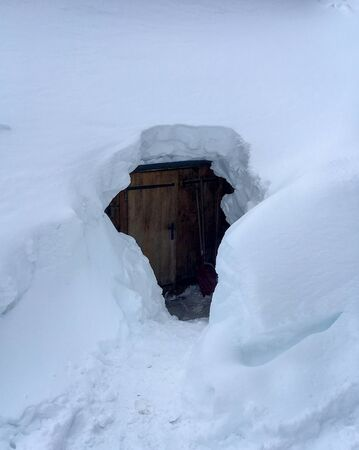 Door of snow covered mountain hut old farmhouse in the Austrian alps