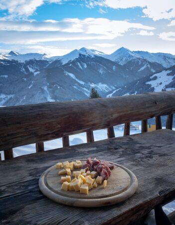 Wooden board with cheese and sausage on a balcony in front of snow covered mountains in the Austrian alps in winter