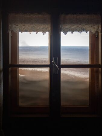 View from inside a snow covered mountain hut through a window with snow in front