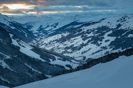 Scenic view of snow covered mountains in the ski region of Saalbach Hinterglemm in the Austria alps against cloudy sky at sunset