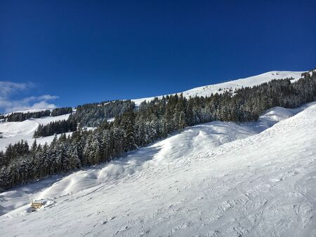 Scenic view of ski slope in the region of Saalbach-Hinterglemm against blue sky