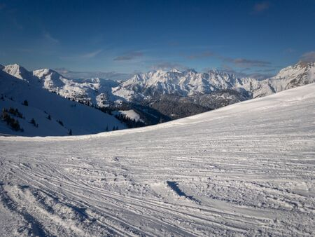 Ski slope and scenic view of snow covered mountains of Lofer Mountains in the Austria alps against blue sky