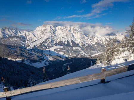 Scenic view of snow covered Leogang mountains wrapped in clouds in the Austrain alps against blue sky Zdjęcie Seryjne