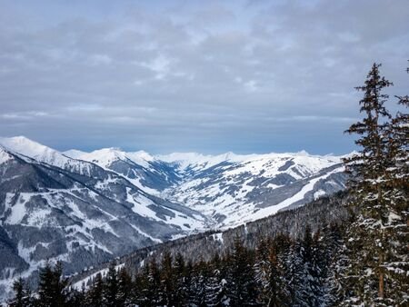 Scenic view of snow covered mountains in the ski region of Saalbach Hinterglemm in the Austria alps against cloudy sky