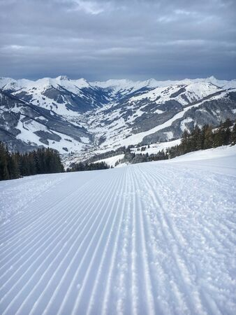 Well prepared ski slope and scenic view of Saalbach Hinterglemm region in the Austria alps against cloudy sky