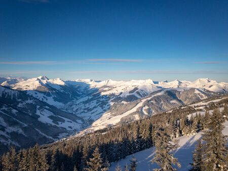 Scenic view of snow covered mountains in the ski region of Saalbach Hinterglemm in the Austria alps against blue sky in the morning
