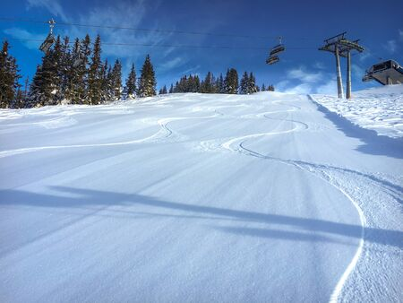 Three single traces at ski slope underneath a chairlift in the Austrian alps against blue sky Zdjęcie Seryjne