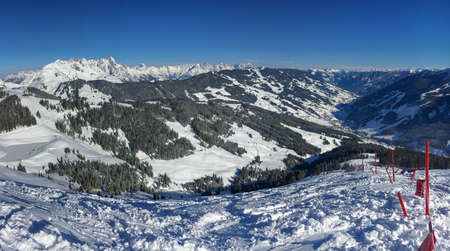 Panoramic view of snow covered mountains in the ski region of Saalbach Hinterglemm in the Austria alps against blue sky Publikacyjne