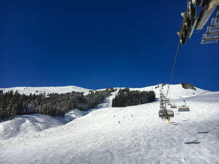 Scenic view of ski slope in the region of Saalbach-Hinterglemm seen from a chairlift against blue sky Publikacyjne