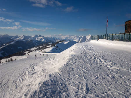 Ski slope and scenic view of snow covered mountains in the region of Saalbach Hinterglemm in the Austria alps against blue sky Publikacyjne