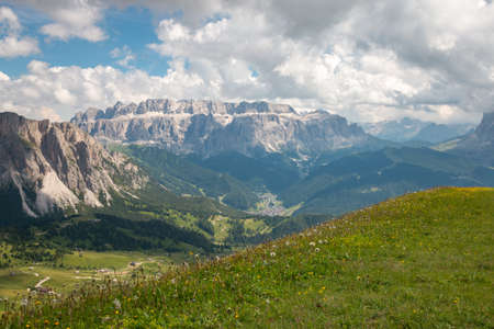 Scenic view of Sella group mountains with dandelion in the foreground seen from Seceda mountain, Dolomites, Trentino Alto Adige, South Tyrol, Italy