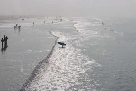 People walking on north sea beach in Sankt Peter-Ording, Germany next to surf in autumn against sky