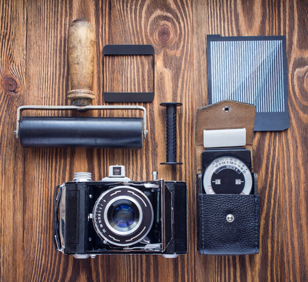reversed: vintage camera,exposure meter and another trappings of film photography. photographers desk Stock Photo
