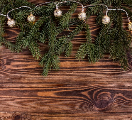 square composition: christmas square composition with vintage garland and fir branches on wooden background. string lights