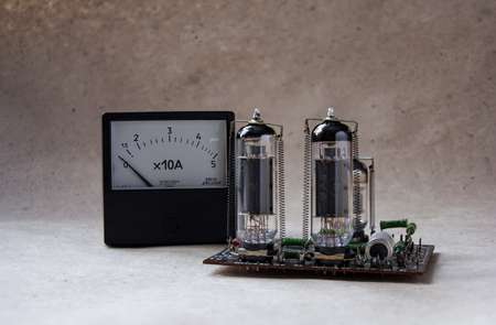 amp: composition from of tube amplifier and vintage ammeter. electronic background
