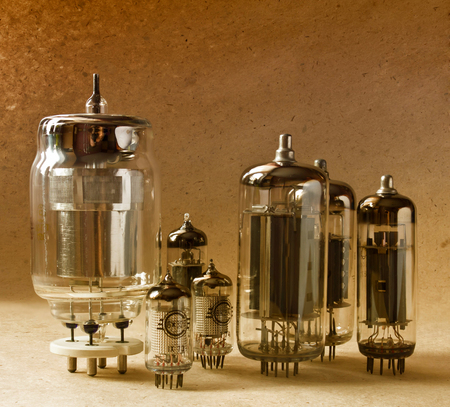 composition of different electronic vacuum tubes on kraft paper background in warm colours.