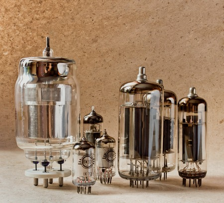 amp: different electronic vacuum tubes on kraft paper background in warm colours. Stock Photo