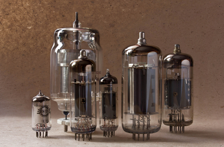composition of vintage electronic vacuum tubes on kraft paper background.