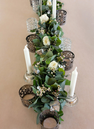 Elegant wedding floral decoration with white candles,roses and eucalyptus.