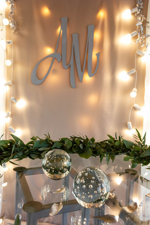 Decoration of wedding registration desk. Glass sphere, strings of lights and wreath of leaves