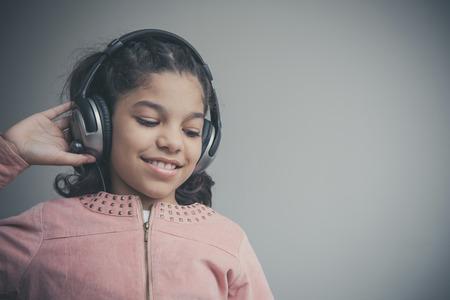 child laughing: Beautiful girl listening to music on her headphones and happy.   Stock Photo
