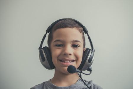 niños riendose: Niño hermoso escuchar música en sus auriculares y feliz.
