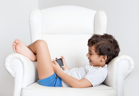boy sitting: Little boy on the sofa playing on mobile.
