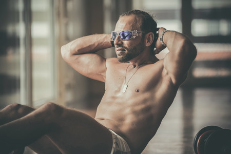 well build: Man doing sit-ups Man exercising at the gym Stock Photo