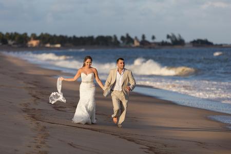 45820035: Wedding on the beach, groom and bride running. Stock Photo