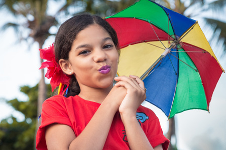 Girl sending kiss  Girl at carnival holding a colorful umbrella and sending kiss Stock Photo